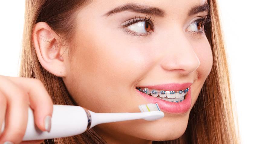 Girl with braces brushing teeth